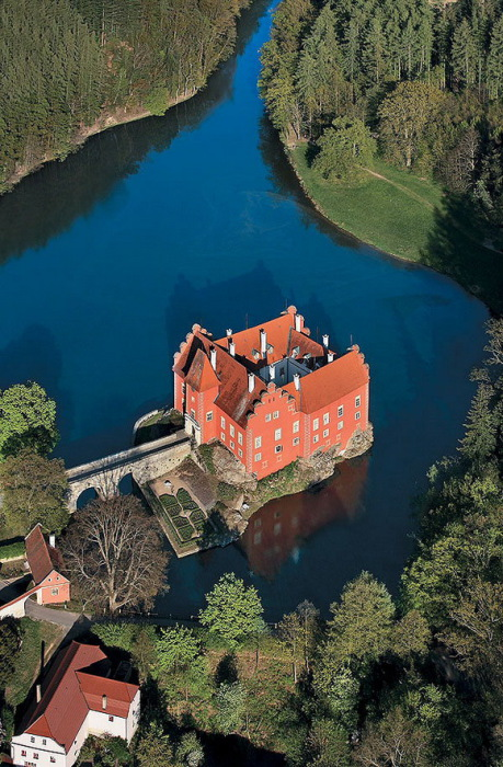Двухэтажный замок возвышающийся на скалистом острове посреди озера.